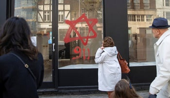 People look at anti-Semitic graffiti on a shop window in Belsize Park, North London, December 29, 2019.