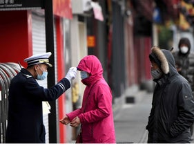 A security guard checks the temperature of people entering Yu Park in Shanghai, China, February 6, 2020.