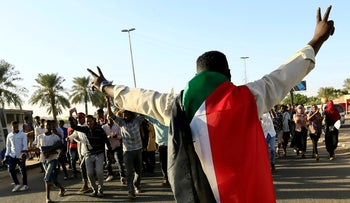 A Sudanese man wears a national flag as people gather during the first anniversary of the uprising that toppled long-time ruler Omar al-Bashir, in Khartoum, Sudan December 19, 2019.