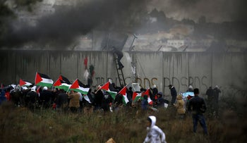 A Palestinian protester scales the security wall as others burn tires during a demonstration against a U.S.-brokered peace proposal, in the West Bank village of Bilin near Ramallah, February 7, 2020.
