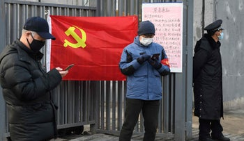 People wearing protective face masks as they stand near a Communist Party flag at the entrance to a residential compound in Beijing, February 9, 2020.