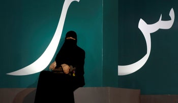 A woman sets under a banner with Arabic letters during a cultural and educational event at the Water Front Park in Jiddah, Saudi Arabia, January 15, 2020