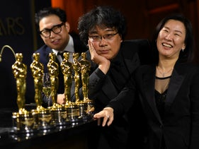 South Korean screenwriter Han Jin-won, South Korean film director Bong Joon Ho and producer Kwak Sin-ae pose with their awards at the 92nd Oscars Governors Ball in Hollywood, California, February 9, 2020.