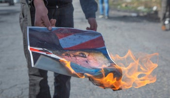 A Palestinian protester burns a poster with a picture of Trump during clashes in the West Bank city of Ramallah, January 30, 2020.