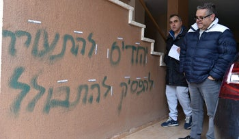 "Residents look at graffiti that says ""Jews, wake up"" and ""Enough with the assimilation"" in the Arab town of Gush Halav, northern Israel, February 11, 2020"