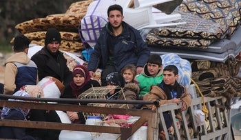 Syrian refugees head northwest through the town of Hazano in Idlib province as the flee renewed fighting Monday, Jan. 27, 2020