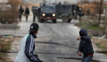 Palestinian demonstrators throws stones during clashes with Israeli security forces, Beit El checkpoint, Saturday, February 1, 2020