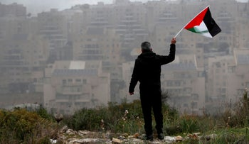 A demonstrator holds a Palestinian flag in front of the settlement of Modi'in Illit in the village of Bilin in the West Bank February 7, 2020.