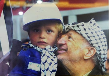 Yasser Arafat holds a 2-year-old Mohammed Tamimi in his arms.