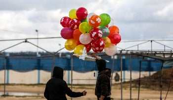 Masked Palestinians prepare to release an incendiary device near Gaza's Bureij refugee camp, along the Israel-Gaza border fence, on February 10, 2020