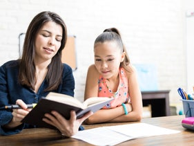 Female student listening to private teacher reading book at table in home.