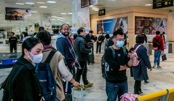 Passengers, wearing masks, gather their luggage as they prepare to exit the Aswan International Airport in the Egyptian city, some 920 kms south of the capital Cairo, on February 2, 2020.