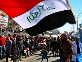 A woman waves an Iraqi flag during a protest in Tahrir Square, Baghdad, Iraq, February 13, 2020