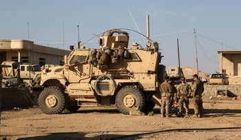U.S. Army soldiers stand outside their armored vehicle on a joint base with Iraqi army south of Mosul, Iraq, February 23, 2017.