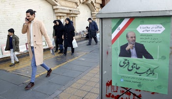 Iranians walk past an electoral poster of a candidate of the upcoming parliamentary elections on a street in Tehran, February 12, 2020.