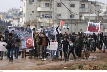 People march with portraits of killed Turkish-backed Syrian fighters and flags of Turkey and of the Syrian opposition as they demonstrate by a Turkish military observation post in the town of Binnish in Idlib province, February 14, 2020.