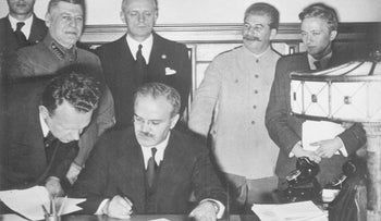 Soviet Foreign Minister Vyacheslav Molotov signs the German–Soviet Treaty of Friendship in Moscow, September 28, 1939; behind him among others are Joachim von Ribbentrop and Joseph Stalin