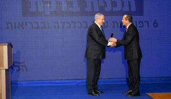 Nir Barkat, right, taking the stage at the Tel Aviv Stock Exchange to announce the Likud's economic plan