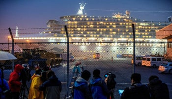 A bus arrives near the cruise ship Diamond Princess, where dozens of passengers tested positive for coronavirus, in Yokohama, Japan, February 16, 2020.