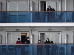 Passengers look out from the balconies of the Diamond Princess cruise ship in quarantine due to fears of the COVID-19 coronavirus, Cruise Terminal in Yokohama, February 19, 2020.