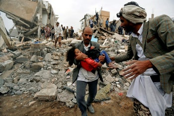 A man carries Buthaina Muhammad Mansour, believed to be four or five, rescued from the site of a Saudi-led air strike that killed eight of her family members in Sanaa, Yemen, August 25, 2017.