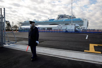 A security guard stands at the entrance to Yokohama port as the quarantined Diamond Princess cruise ship is seen in the background Wednesday, February 19, 2020