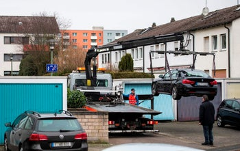 A car that allegedly belongs to a suspect in a killing is lifted on a truck, near the home of the suspect in Hanau, western Germany, February 20, 2020