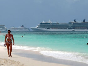A woman walks along Seven Mile Beach with three cruise ships anchored in port in George Town, Cayman Islands, April 27, 2010