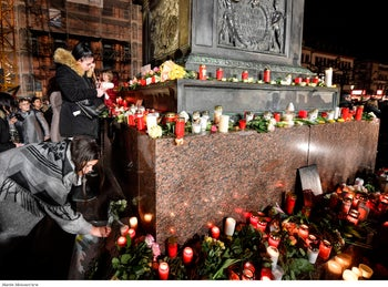 People place candles and flowers at a monument on the market place during a mourning for the victims of the shooting in Hanau, Germany, February 20, 2020.