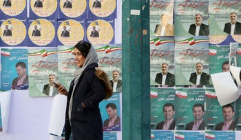 An Iranian woman walks past an electoral poster in a street of the capital Tehran ahead of this week's parliamentary elections on February 18, 2020.