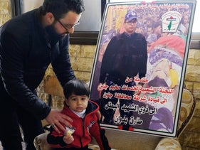 Sgt. Tarek Badwan's son, Tayim, stands next a memorial poster for his father.