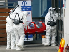 Medical workers wearing protective gear carry a patient infected with coronavirus at a hospital in Chuncheon, South korea, February 22, 2020.