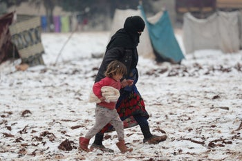 An internally displaced woman holds the hand of a child carrying bread, as they walk on snow at a makeshift camp in Azaz, Syria February 13, 2020.