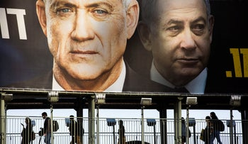People walk on a bridge under an election campaign billboard for the Blue and White party, the opposition party led by Benny Gantz, left, in Ramat Gan, Israel, February 18, 2020