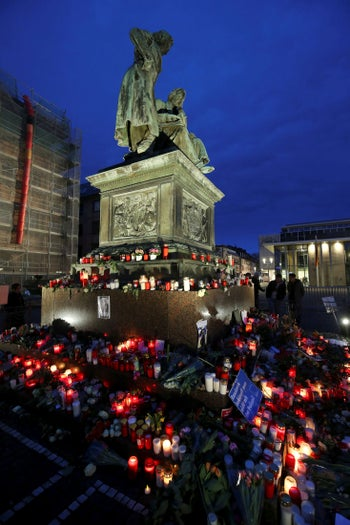 Candles and flowers are placed at the Brothers Grimm monument for the victims of the recent shooting in Hanau, near Frankfurt, Germany, February 22, 2020
