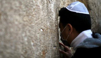 A man wears a face mask as he visits the Western Wall, the holiest site where Jews can pray, in Jerusalem's old city. Feb. 16, 2020