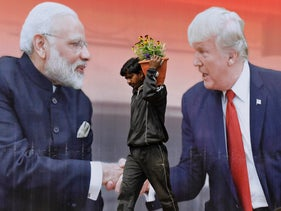 An Indian worker carrying flower posts walks past a billboard featuring U.S. President Donald Trump and Indian Prime Minister Narendra Modi, in Agra, India. Feb. 23, 2020