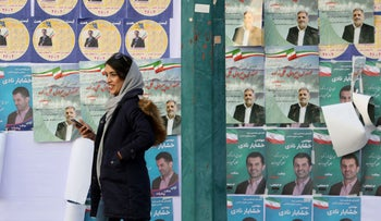 An Iranian woman walks past election posters on a street of the capital, Tehran, ahead of parliamentary elections.