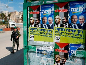 A member of the Israeli security forces walks past election posters in the West Bank town of Hebron on February 23, 2020.