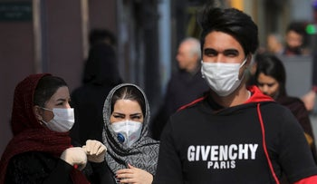 Pedestrians wear masks to help guard against the Coronavirus, in downtown Tehran, Iran, Sunday, Feb. 23, 2020