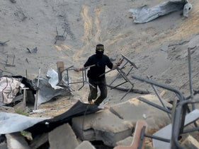 A Palestinian militant carries chairs as he surveys an Islamic Jihad site that was targeted in an Israeli air strike in the southern Gaza Strip, February 24, 2020