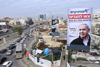 People walking next to election campaign billboards for Likud and Kahol Lavan in Bnei Brak, central Israel, February 23, 2020.