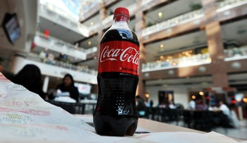 A bottle of Coca Cola is pictured as people have lunch at a shopping mall in Arlington, Virgina, in this February 15, 2011 file photo.