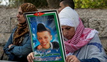 A woman holds a picture of murdered Palestinian teen Mohammed Abu Khdeir outside a court, in 2015.