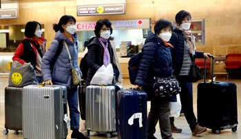 Tourists from Korea wearing protective masks at the Ben Gurion airport near Tel Aviv, Israel, February 24, 2020.