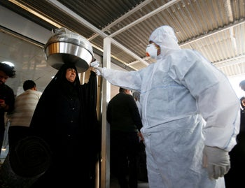 Iraqi medical staff check a passenger's temperature, amid the new coronavirus outbreak, upon her arrival to Shalamcha Border Crossing between Iraq and Iran, February 20, 2020