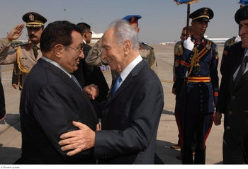 Egyptian President Hosni Mubarak welcomes Israeli President Shimon Peres at Sharm el Sheikh airport, 2009.