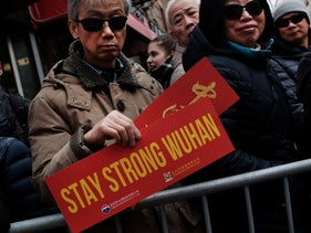 "Holding signs saying ""Wuhan stay strong"" people watch the annual Lunar New Year Parade in Manhattan's Chinatown on February 09, 2020 in New York City."