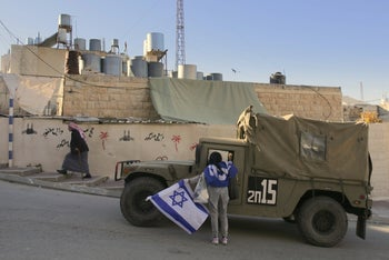A woman waving the Israeli flag speaking to a soldier in a military jeep in Hebron as a Palestinian woman walks by in the background.