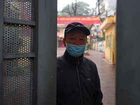 A security staff stands at the entrance of a primary school closed to prevent the spread of corona virus in Hanoi on February 3, 2020.